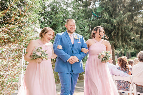 Groomsman in bright blue suits leads two bridesmaids in pink dresses down the aisle.