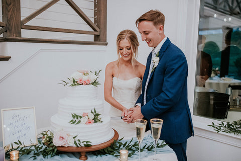 Bride and Groom smiling as they cut the wedding cake. It is a three-tier cake decorated with flowers and greenery.