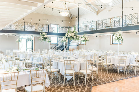 Photo of wedding reception dining room. The tables are set up with chiavari chairs and twinkly lights hanging from the ceiling.