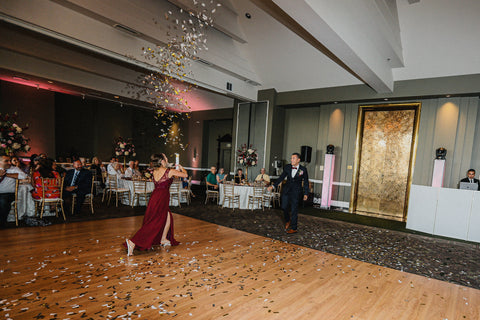 Bridesmaid and Groomsman throwing confetti in the air during the Grand March.