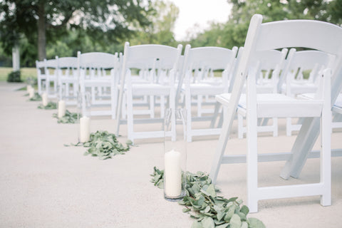 Rows of white wooden folding chairs lined up for a wedding ceremony. White candles and greenery lined up in the aisle.