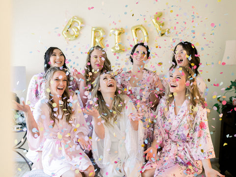 Bride and Bridesmaids dressed in cute robes. They are taking a fun group picture with confetti flying in the air.