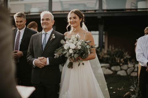 Bride and her father are smiling as they walk down the aisle.