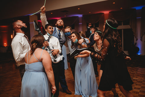 Group of Bridesmaids and Groomsmen in a circle enthusiastically singing the song. They have light up necklaces and blow-up guitars.
