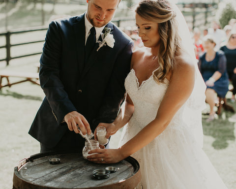 Bride and Groom pouring sand into a vessel during a unity ceremony.