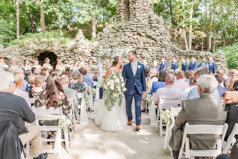 Bride and Groom smiling at each other as they walk down the aisle. Outdoor ceremony with a brick wall and white wooden chairs.