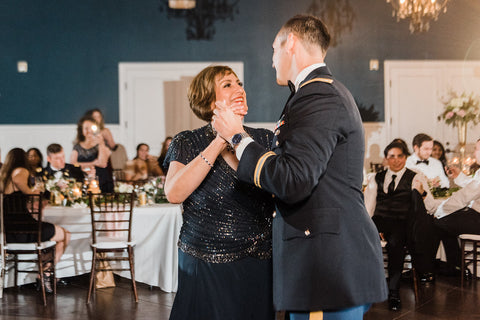 Groom and his mother smiling as they're dancing during the Mother/ Son Dance.