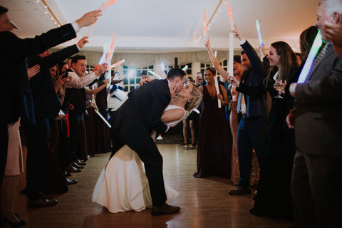 Bride and Groom dipping for a kiss with friends and loved ones cheering.