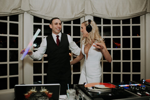 Bride and Groom jamming out together behind the DJ table.