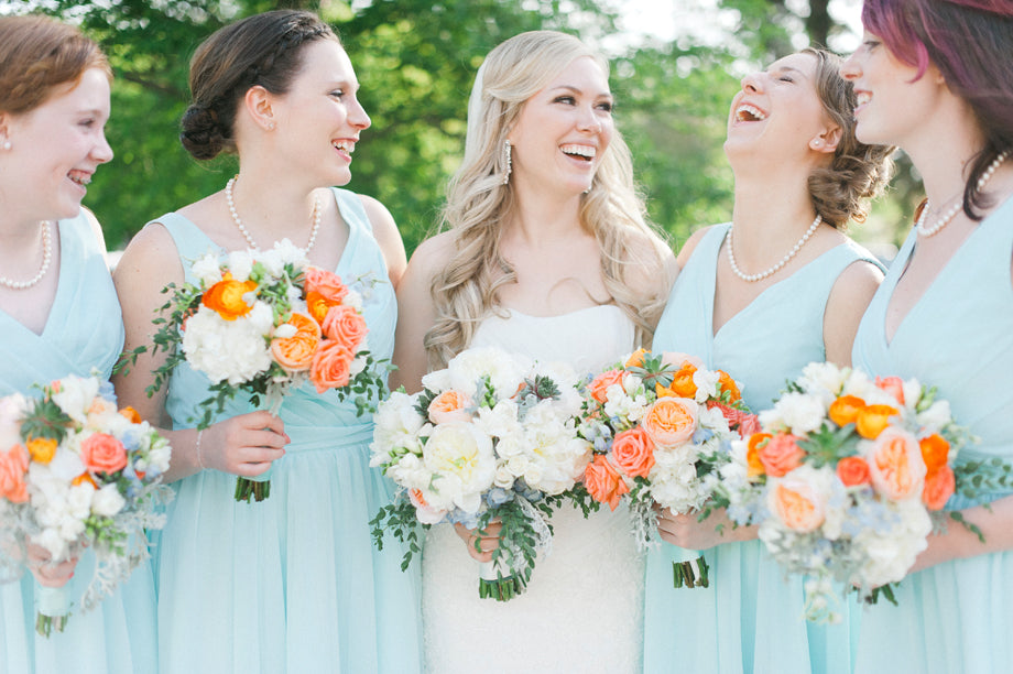 Chiffon mint bridesmaid dresses with vibrant orange bridal bouquets | Melissa Oholendt Photography | Kennedy Blue