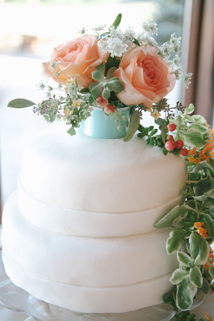 A simple white wedding cake with decorative flowers. | An Outdoor Wedding That's Simply Charming | Kennedy Blue