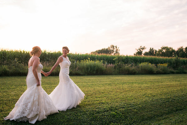 lesbian couple holding hands in bridal gowns | How to Plan Your Wedding Party for Your Gay Wedding