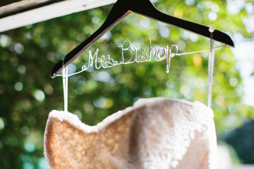 A lace wedding dress on a personalzied hanger | A Chic Purple and Gold Pittsburgh Wedding