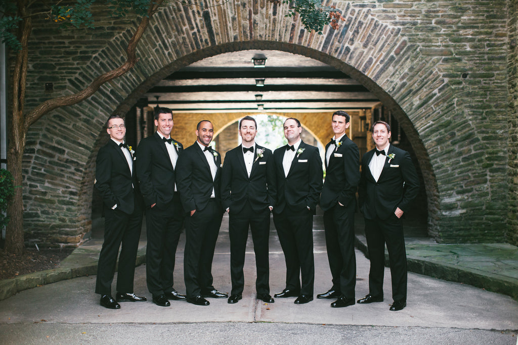 The groom and groomsmen wore black suits and bowties | A Chic Purple and Gold Pittsburgh Wedding