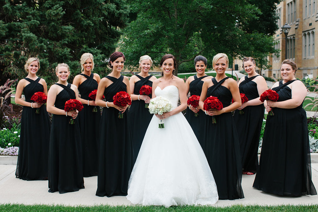 These bridesmaids were gorgeous in their Kennedy Blue black bridesmaid dresses and red rose bouquets! | A Timeless and Traditional Mansion Wedding
