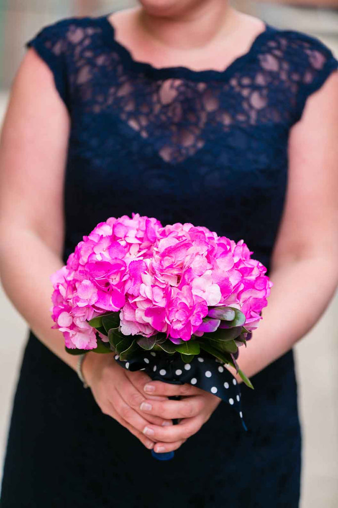 A navy lace bridesmaid dress with a vibrant pink bouquet | A Blue and Pink Rock 'n Roll Wedding