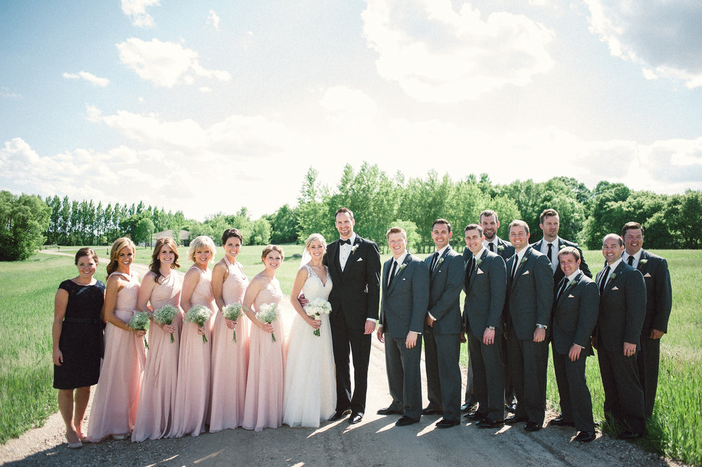 Blush pink bridesmaid dresses with dark grey suits.