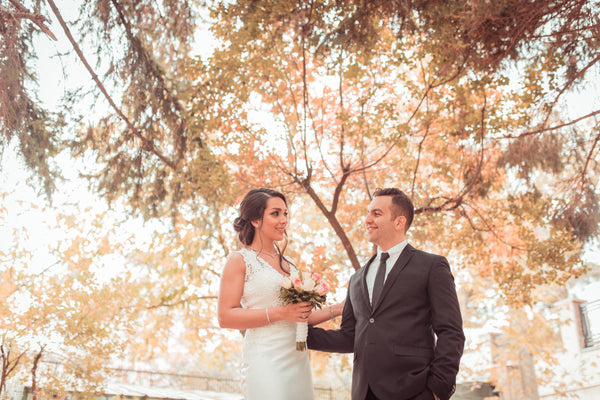 couple standing in front of trees outside | How to Find a Wedding Officiant