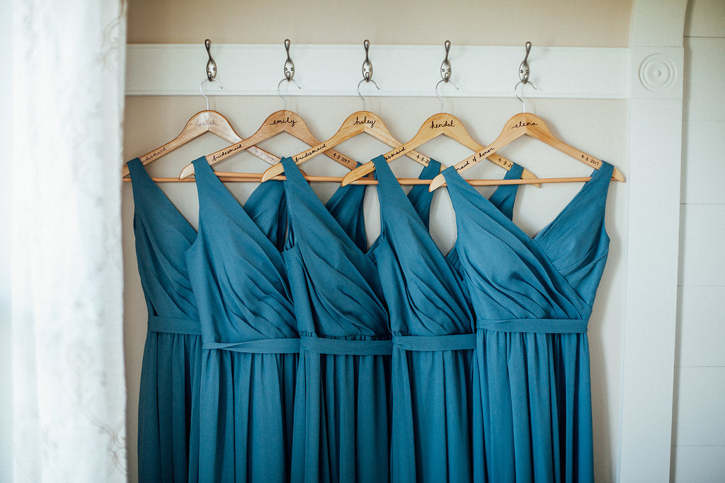 Teal-Bridesmaid-Dresses-hanging-customized-hangers-Emily-Caleb-Featured-BrideStory-Real-Wedding