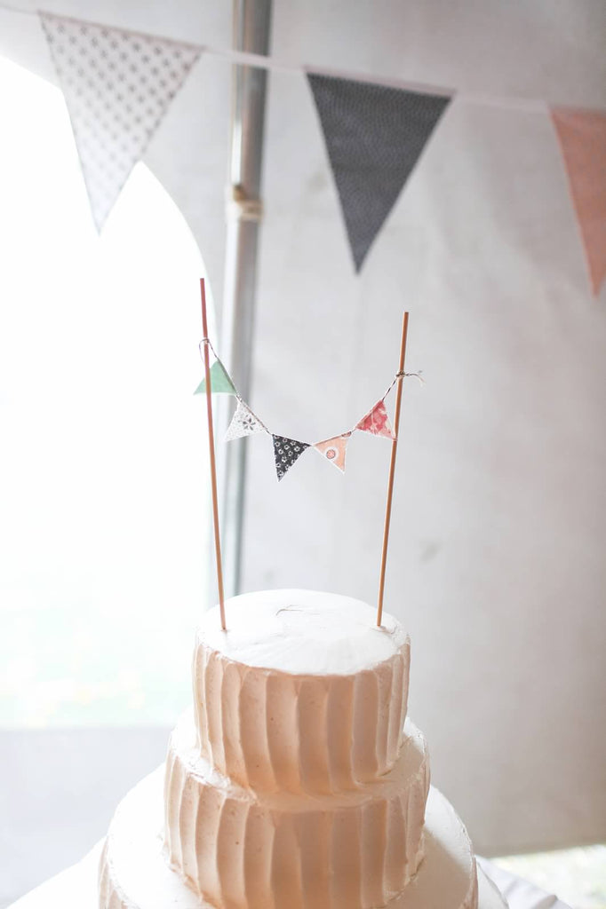A simple wedding cake with a bunting cake topper. | A Whimsical Autumn Wedding | See the full gallery here!