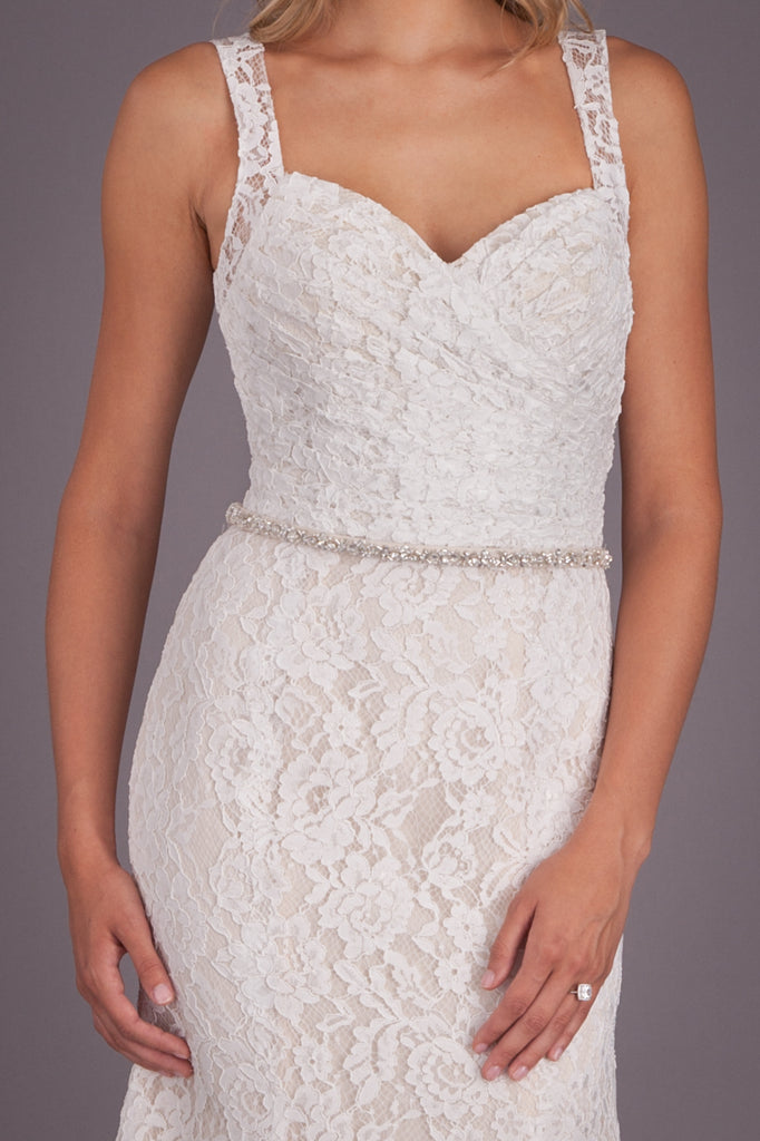 We love the lace detail and slim, beaded belt on this fitted, lace bridal gown. | Featured Style: A Lace, Open-Back Wedding Dress