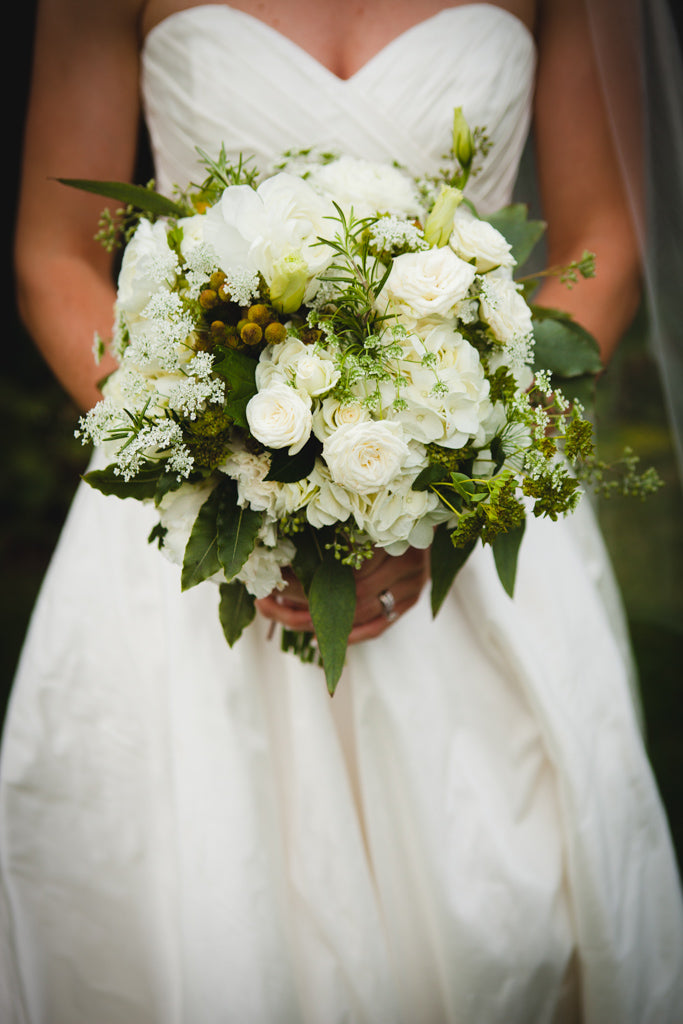 A white and green bouquet for the bride. | A Simple Wedding Dress for a Lakeside Ceremony