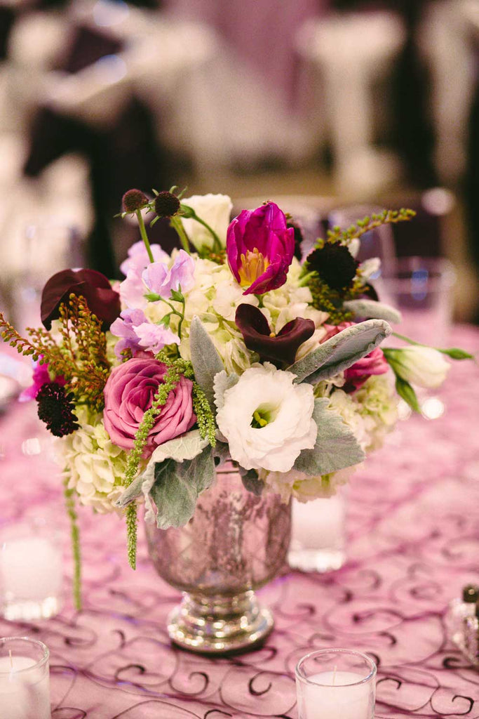 Make double use out of the bridesmaid bouquets by incorporating them into the table centerpieces.