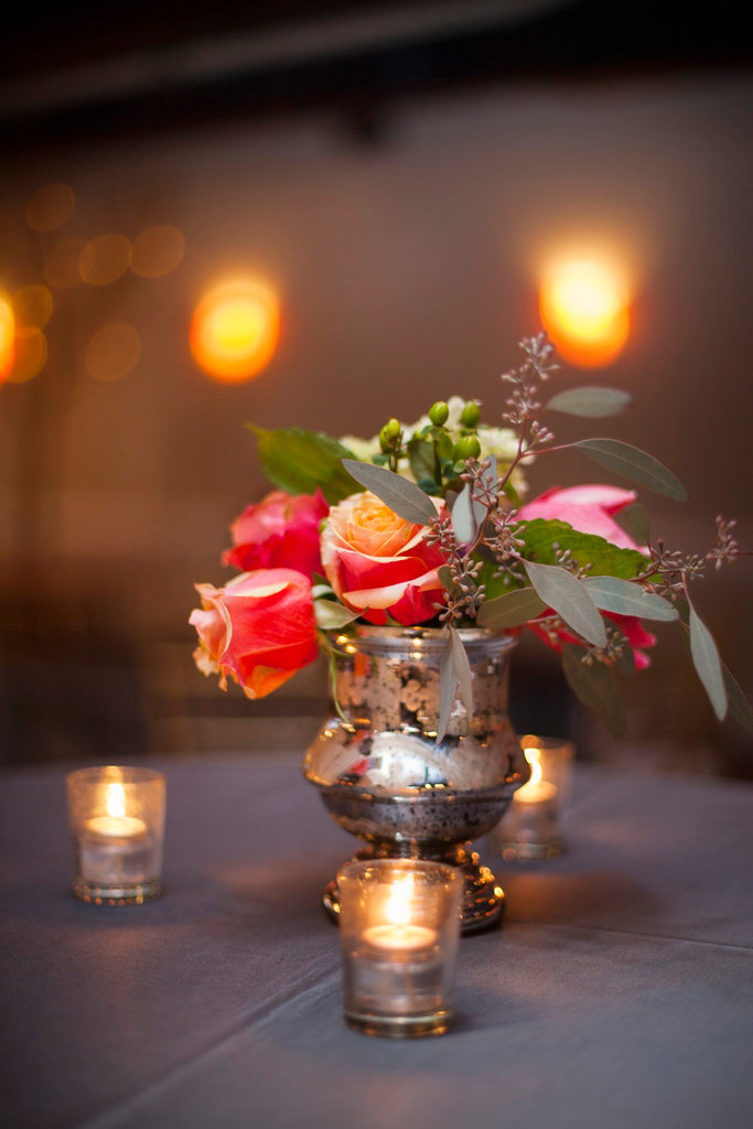 A gorgeous winter bouquet with silver votives make for a gorgeous wedding centerpiece. | A Romantic Winter-Themed Wedding