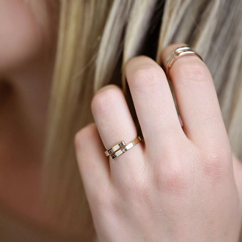 two stackable gold name rings on girls finger - Our Coordinates