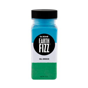 Small, clear plastic jar filled with color block blue, white and green bath fizz that smells like sea breeze. Each shot contains a fun surprise.