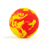 Red and yellow swirl round bath bomb out of packaging on white background.
