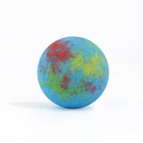Multi-color round bath bomb out of packaging on white background.