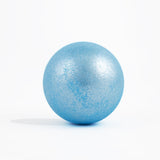 Sparkly light blue round bath bomb out of packaging on white background.