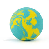 Yellow and teal swirl round bath bomb out of packaging on white background.