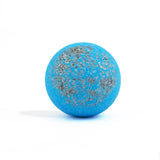 Blue with silver topping round bath bomb out of packaging on white background.