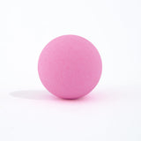 Pink round bath bomb out of packaging on white background.