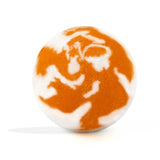 White and orange swirl round bath bomb out of packaging on white background.