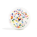 White with multicolor sprinkles round bath bomb out of packaging on white background.