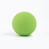 Green round bath bomb out of packaging on white background.