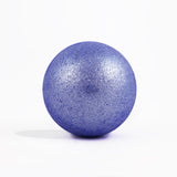 Sparkly purple round bath bomb out of packaging on white background.