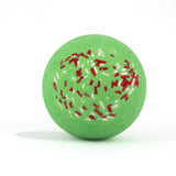 Green with red and white sprinkles, round bath bomb out of packaging on white background.