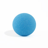 Blue round bath bomb out of packaging on white background.