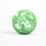Green and white swirl round bath bomb out of packaging on white background.