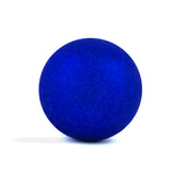 Sparkly navy round bath bomb out of packaging on white background.
