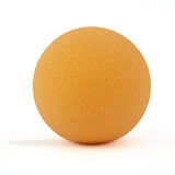 Orange round bath bomb out of packaging on white background.