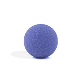 Purple round bath bomb out of packaging on white background.