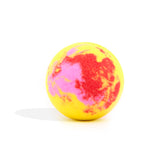Yellow, red and pink round bath bomb out of packaging on white background.