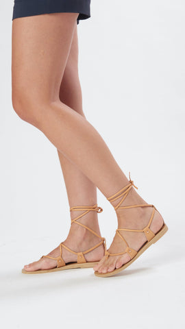 The Lia Sandal in light tan is a strappy shoe that features a lace-up ankle detail and has tassel details to give you the gladiator feel.