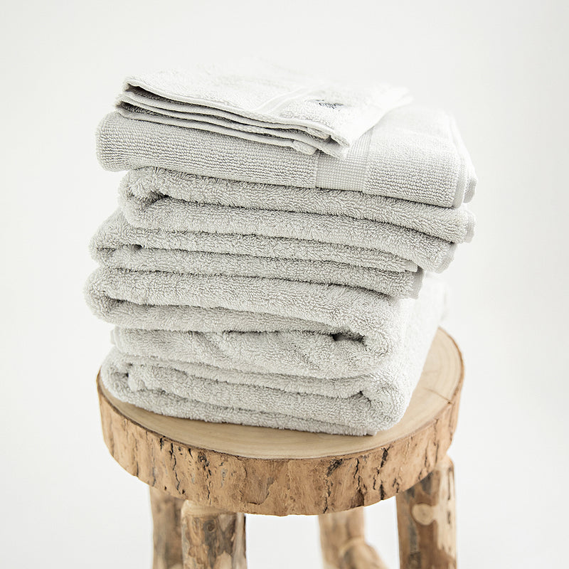 7 piece organic towel set in 700GSM Stone. 2 bath towels, 2 hand towels, 2 face towels and one bath mat. Stacked on a stool.