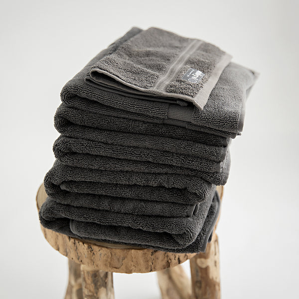 7 piece organic towel set in 700GSM charcoal. 2 bath towels, 2 hand towels, 2 face towels and one bath mat. Stacked on stool.